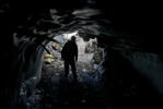A miner enters an ice tunnel which leads to a mine.