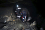 Miners work inside a mine.
