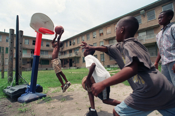 Several local boys make do with a toy basketball goal and high spirits.