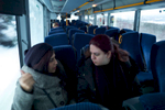 Two female asylum seekers sit talking on a bus that is en route to a refugee camp.