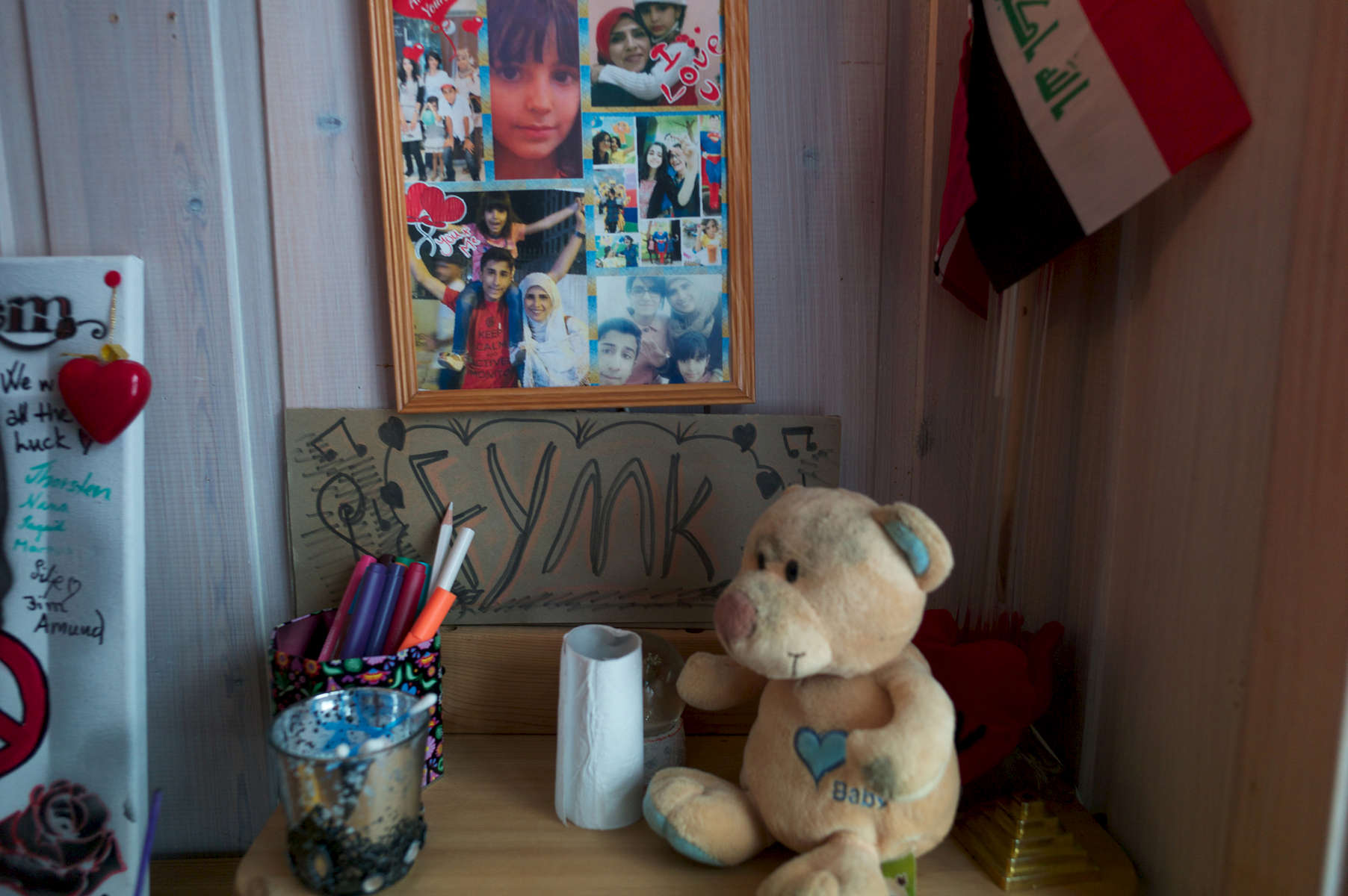 A wall and desk that has family photos and a handmade sign.