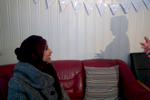 A rejected asylum seeker sits on a sofa talking to an Arabic woman whose only image is that of the shadow she cast on a wall.
