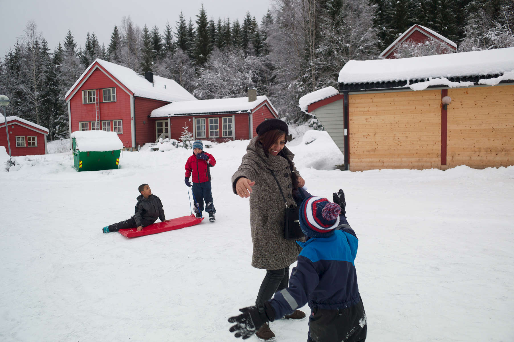 A rejected asylum seeker standing outside in the snow hugs a young child.