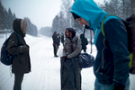 Three rejected asylum seekers (with others in the background) wait at a bus stop in a snow-covered environment.