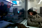 A rejected asylum seeker sleeps on a train as a fellow passenger (who is reflected in the window) approaches her seat.