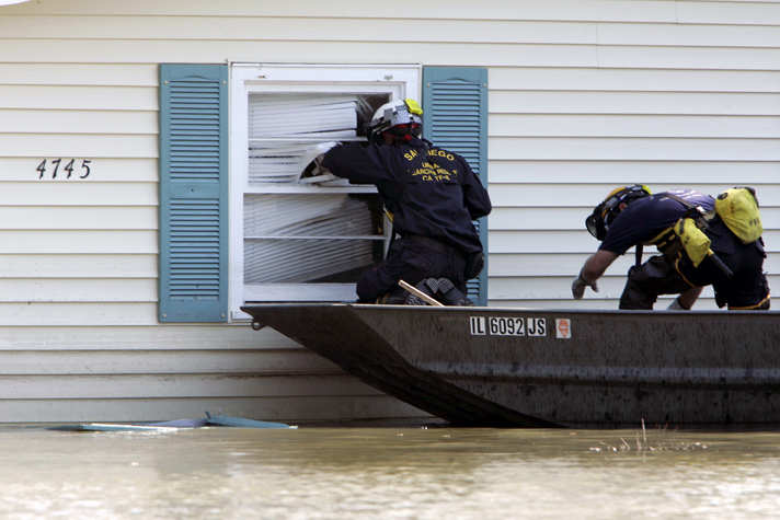 September 11, 2005 - New Orleans, Louisiana -  Members of a San Diego firefighting unit search a home for survivors.