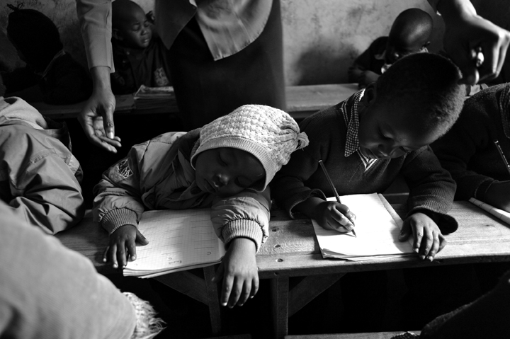 Teacher Nancy Vivian Obanda prepares to wake her baby class student, Stephen Maina, 2 years-9 months old, while Isaac Muriithi, 3-years old, does class work.