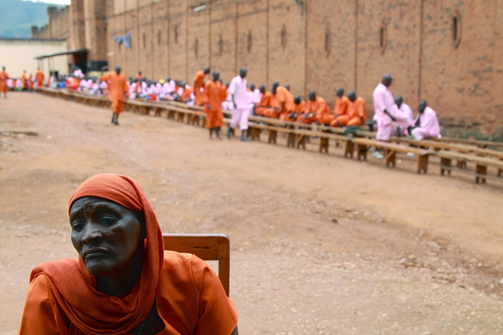 An older Hutu woman sits in a chair outside the walls a prison; there is a group of inmates in the background behind her waiting for visitors.