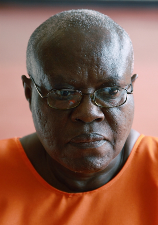Pictured is a head and shoulder shot of a 61-year old Rwandan woman; she's wearing an orange prison uniform.