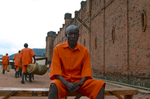 A 47-year old Rwandan man, wearing an orange prison uniform, sits on a wood bench outside the visible prison wall; in the background are other inmates walking away from the camera.