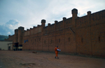 It is a landscape shot showing the outside of a vast prison wall, and the small figure of a single inmate (wearing an orange uniform) walking the grounds.