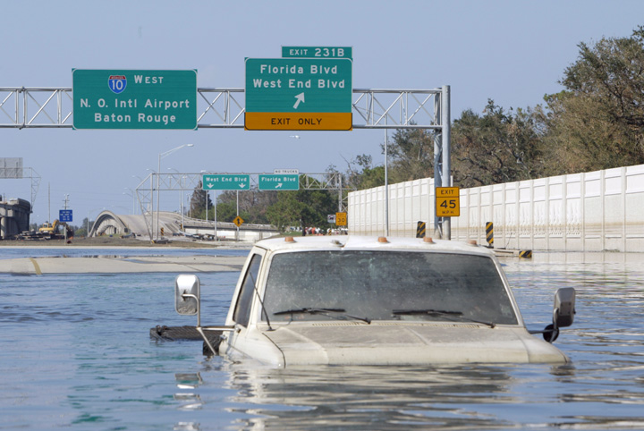 A vehicle, in the foreground, sits in flooded waters with an Interstate 10 West sign in the background.