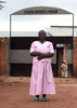 It is a vertical photo of a 64-year old woman, dressed in prison clothing, standing in front of a sign that indicates the name of the prison.
