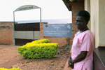 Standing outside a 62-year old woman, dressed in a pink prison uniform, looks into the camera; in the background is a sign with the prison's name.