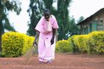 An 83-year old Rwandan woman is bent over as she sweepsT an outside area of the prison; she's wearing a pink prison uniform.