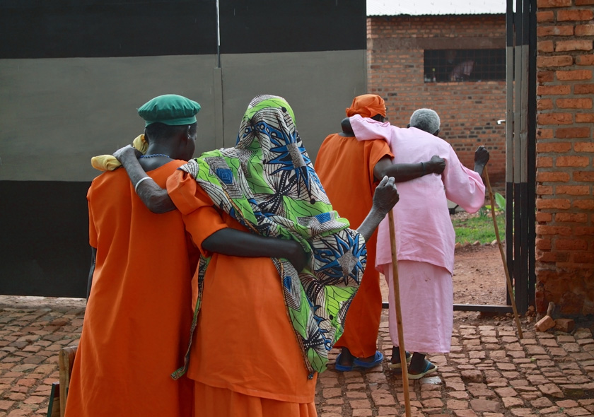 Shown from behind, two elderly Rwandan women are held up by two other elderly women as they walk back to their rooms - all are wearing prison uniforms.