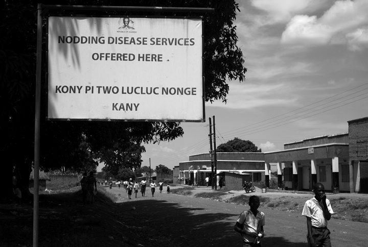 September 15, 2014 - Lubiri Village - Two school children walk pass a sign for the Atanga Health Centre III, which treats Nodding Syndrome victims.