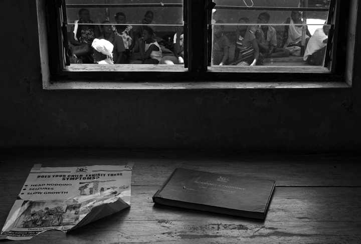 October 3, 2014 - Lubiri Village - Caretakers of Nodding Syndrome patients wait to enter the Atanga Health Centre III. On the desk is a poster which highlights the symptoms of the illness and a patient registry book.
