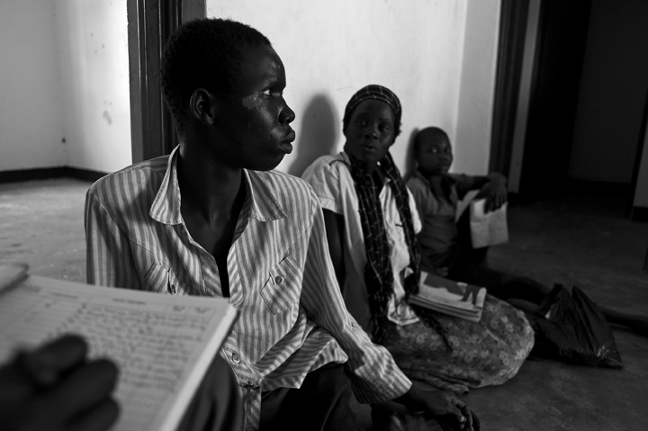 September 11, 2014 - Lapul - Ocwida village - Nodding Syndrome patient Oyoo Maurice, 21, displaying wounds from a recent epileptic seizure (a common symptom of Nodding Syndrome), waits with his caretaker, sister-in-law Atenyo Ester, 30, seated behind, as a medical records assistant reviews his record.