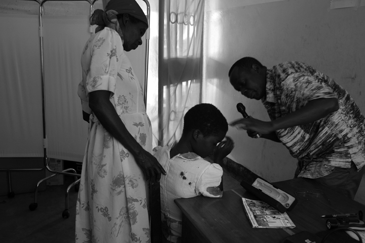 October 3, 2014 - Lubiri Village - Dr. Ben Watmon, an ophthalmologist, tries to examine the eyes of Nodding Syndrome (NS) patient Lamwaka Monica, 15; unable to understand what the doctor was trying to do she refused to cooperate, even with her mother, Lalam Rose, nearby. Dr. Watmon is with Gulu Hospital and is at the health centre on an outreach visit to assist NS patients. NS is a mysterious and devastating neurologic condition which stunts growth, causes its victims to nod (repeatedly dropping their heads forward), have epileptic seizures, and causes cognitive deterioration. In severe cases it can result in death.