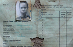 A badly worn Rwandan national identity card is photographed on the ground; the card lists the owner as Tutsis and includes her photograph.