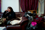 Rejected asylum seeker sitting on sofa using her cellphone.
