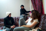 Rejected asylum seeker removes her belongings from behind sofa while seated with two friends.