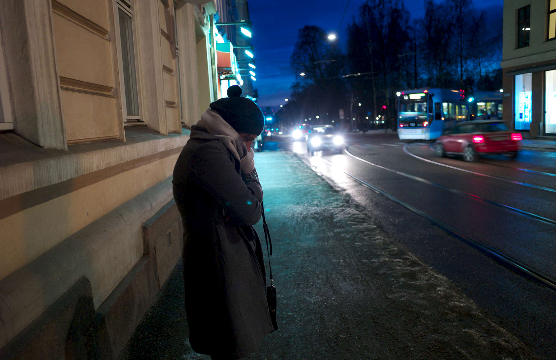 A rejected asylum seeker standing in the cold waits on an isolated street for a driver.