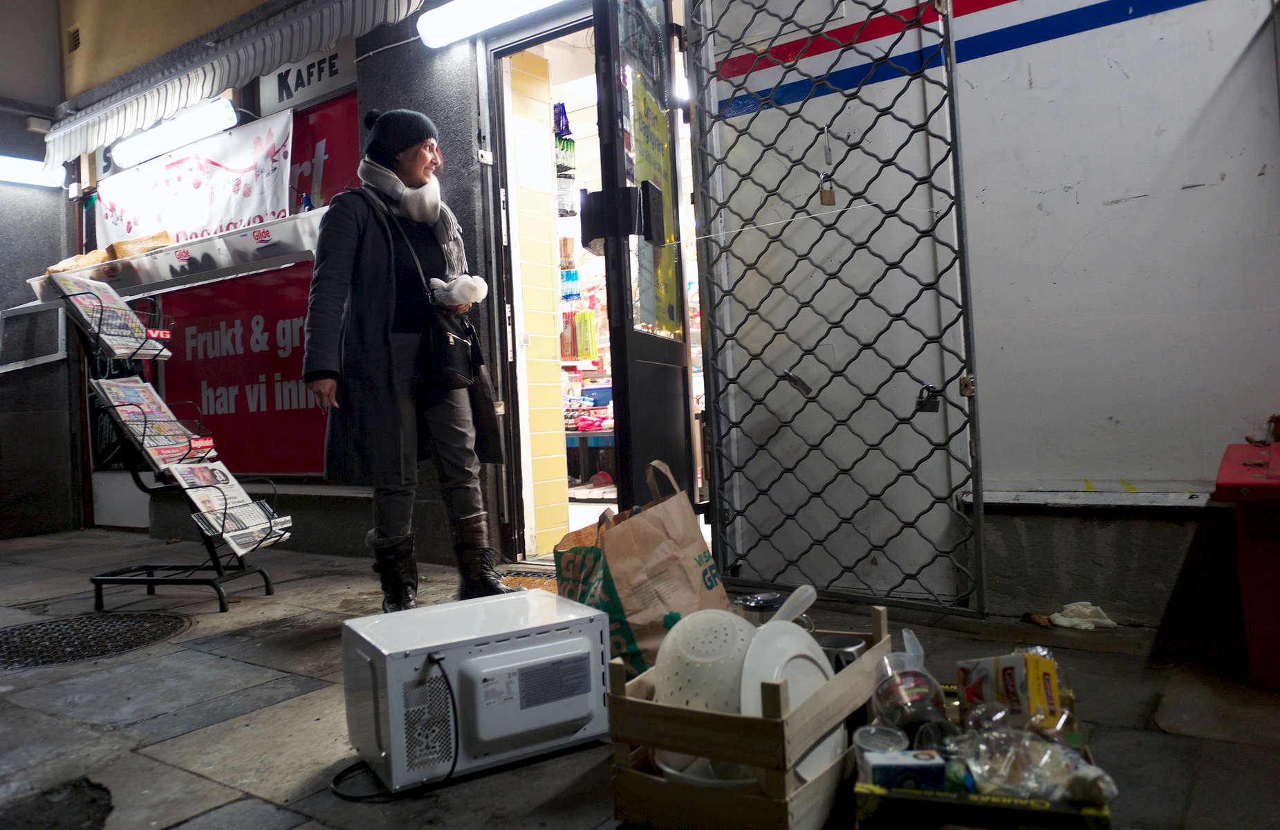 Rejected asylum seeker stands in the doorway of a convenience store with her belongings on the sidewalk.