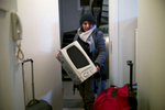 Rejected asylum seeker enters apartment doorway carrying a microwave oven.