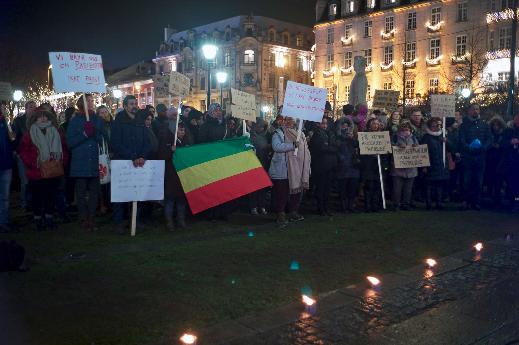 A crowd of protesters, holding signs, stand outside the Parliament building at night demanding justice for asylum seekers.