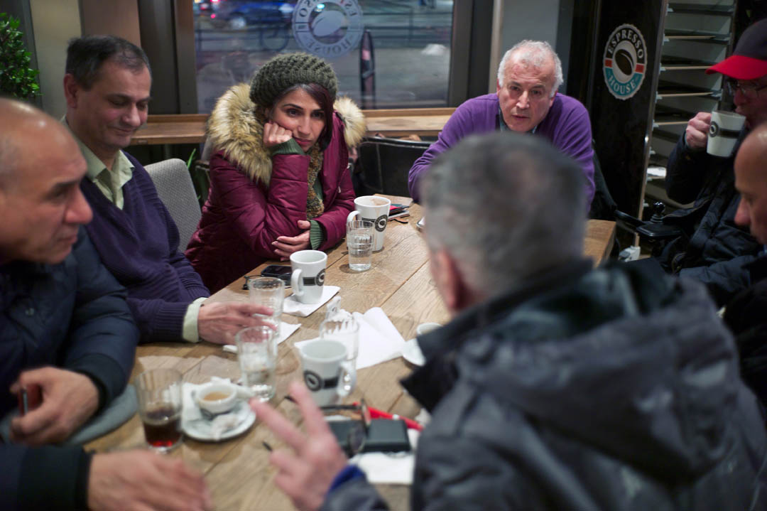 A rejected asylum seeker sitting at a cafe table with six Arabic men listens as one of them proposes marriage.