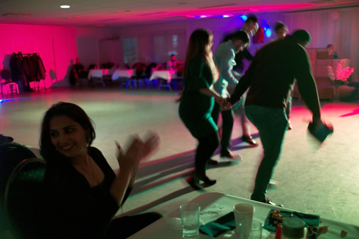 A rejected asylum seeker claps while seated at a table in a darkened room as friends dance in the background.