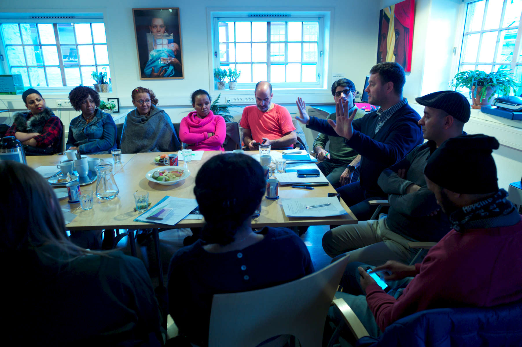 A group of people in a conference room discuss the plight of rejected asylum seekers.