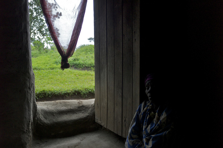 Imelda Gafabusa, 70, falls asleep near her front door while waiting for a rainstorm to end; before the rain she spent four hours working in the field tending to her sweet potato, cassava, and groundnut crops.