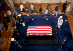 Five soldiers, in full dress uniform, stand around the flag-draped casket of Ronald Reagan, as members of the public (who are blurred) walk pass.