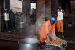 An 58-year old inmate, wearing an orange uniform, cooks a huge pot of beans, in a structure with open walls (nearby other inmates stand observing).