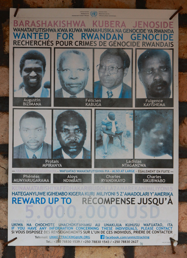 A poster lists the names and faces of five men {quote}Wanted for Rwandan Genocide.{quote}