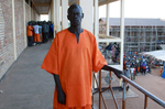A 54-year old Rwandan man stands outside on the second level of a prison building; in the background are numerous inmates grouped on the upper in lower levels.