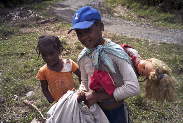 Two young Afro-Bolivian girls, one with a white doll strapped to her back, walk home carrying a sheet filled with oranges (the oranges are not visible).