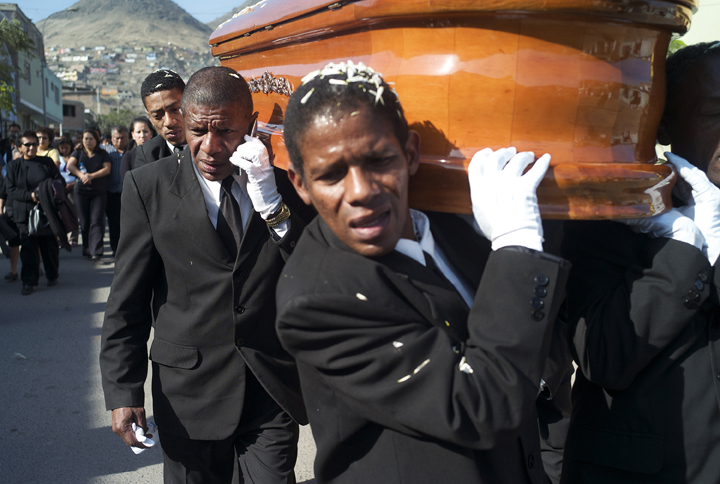 An Afro-Peruvian man, with a casket resting on his shoulder, answers his cellphone during a funeral procession.