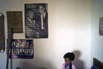 A very young Afro-Bolivian girl is sitting on a bed with her back to a wall that has a poster of Malcolm X and Dr. Martin Luther King, Jr.