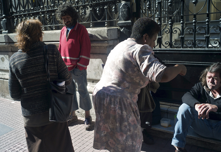Two middle-aged Argentinian women give religious pamphlets to two homeless men (one sitting the other standing) outside a church.