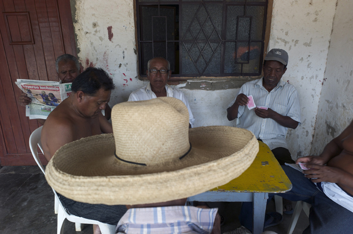 Five Afro-Peruvian are seated on a porch playing cards.