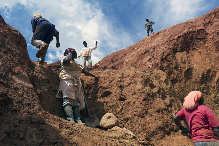 Gold miners wait for buckets of ore to be handed to them at an open-pit mine.