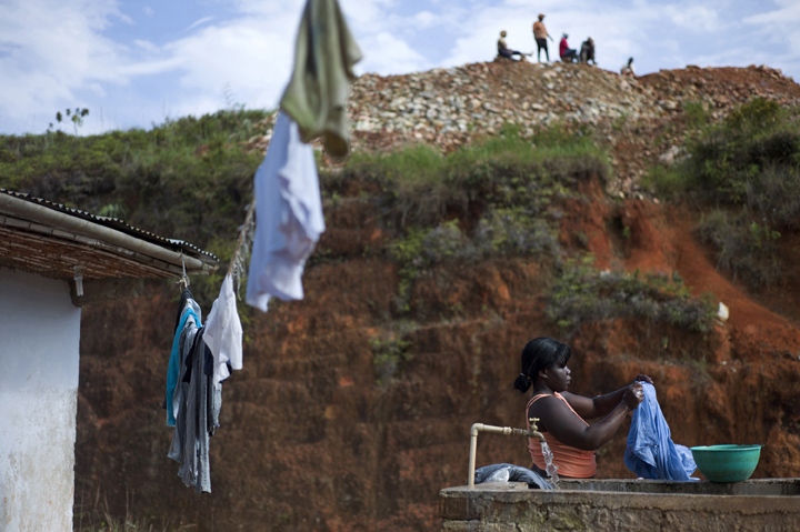 Maria Yuly, 25, washes clothes as several gold miners relax overhead during their morning break.