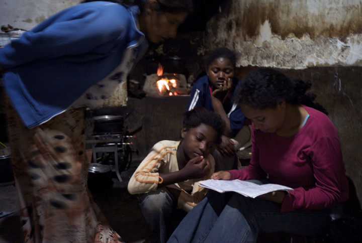 In a darkened room a child sits watching and listening as three women review her school work.