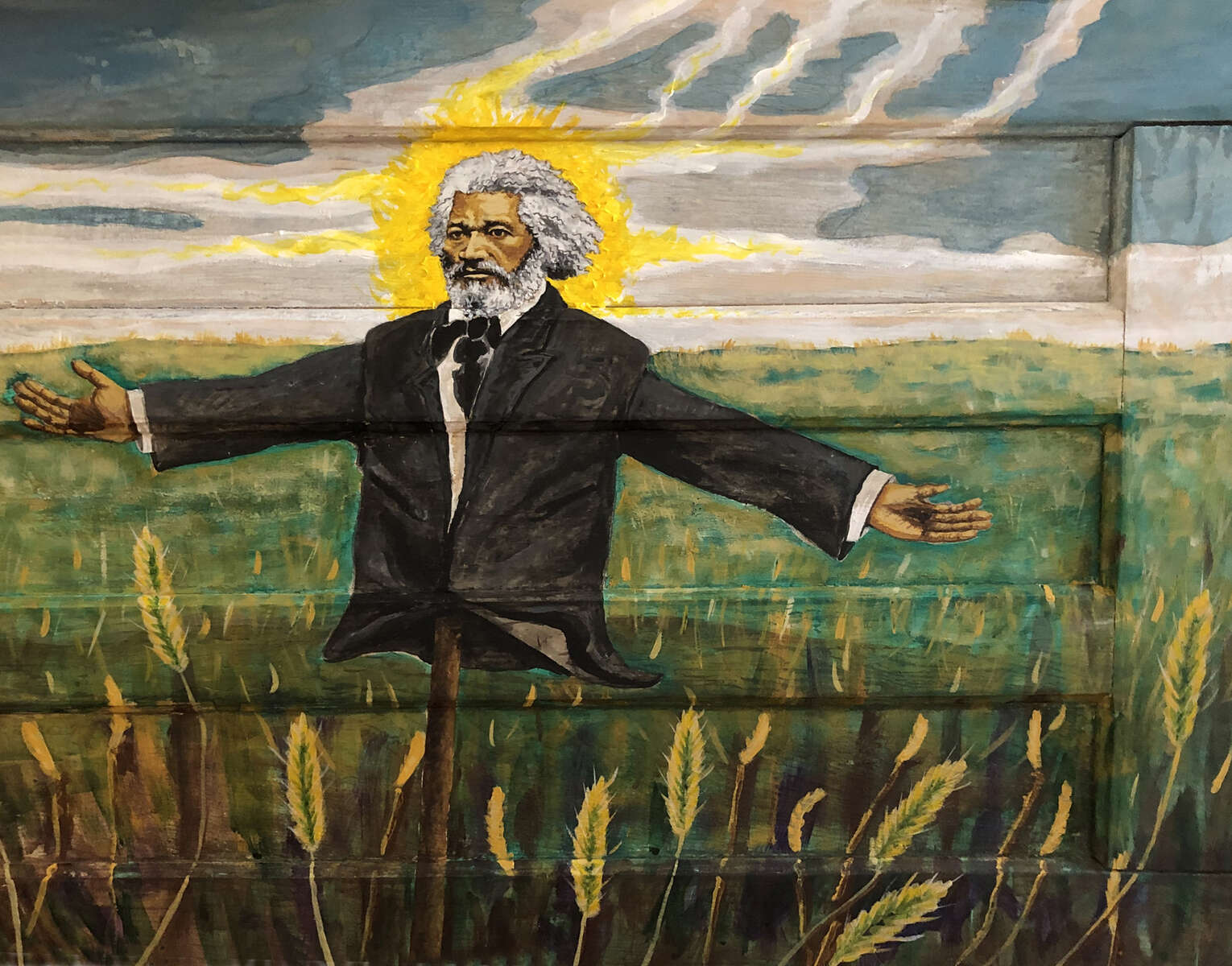 Scarecrows originated in Africa to watch over crops and were symbolic guardians of future generations. Today scarecrows are thought of as totems of death and fear and this speaks of the horrors inflicted upon people of color, but simultaneously represent hope and prosperity. Too many of these living sentinels throughout history have been dismissed and abandoned in a field to wither. This painting was inspired by Frederick Douglass' {quote}What to the Slave is the Fourth of July?{quote}