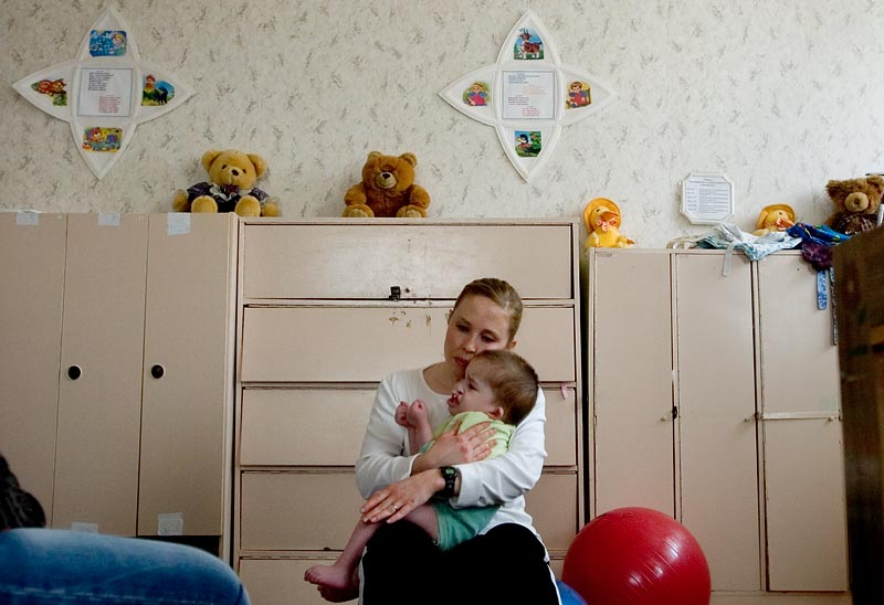 Karen Hairston, a volunteer with the Human Touch Project and a physical therapist at Children's Therapy Services in Fayetteville, Arkansas, tries to comfort Sveta, 3, who cries whenever she is held. Three of Hairston's patients in Arkansas are former Ukrainian orphans with Cerebral Palsy.