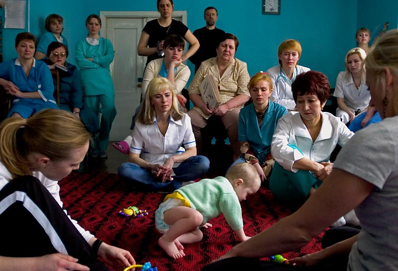 Karen Hairston (foreground left) and Kym Hannah (foreground right), both physical therapists at Children's Therapy Services in Fayetteville, Arkansas, evaluate a child as Ukrainian caretakers observe. Over the course of three days, Hairston and Hannah put together an action plan with exercises and instructions for each special needs child at the orphanage. Future visits by volunteers will gauge the efficacy of both the caretakers' training and the children's treatment.